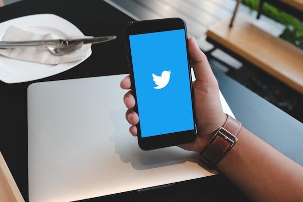 スマートフォンを手に持って、twitterアプリケーションの使用を開始する男のクローズアップ。