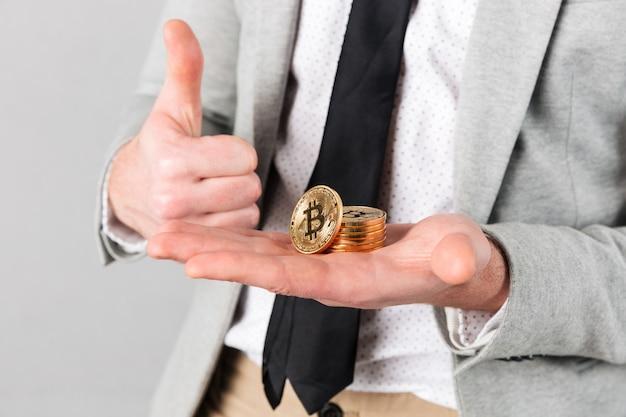 Крупным планом мужчина держит стопку золотых биткойнов
