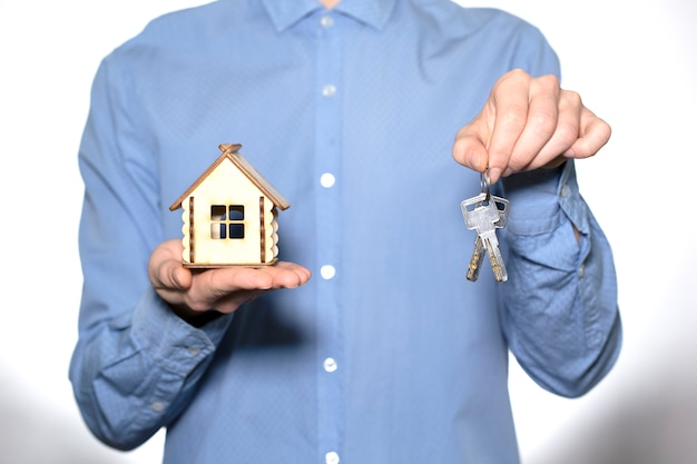 Закройте человека в синей рубашке, держа маленький дом и ключи