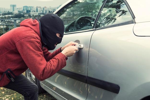 Закройте человека в черной маске грабителя, ломая замок автомобиля на фоне города. злоумышленник взламывает автомобиль отмычкой. злоумышленник вторгается в припаркованный автомобиль. преступное покушение.