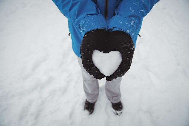 雪の心を持って暖かい服を着た男のクローズアップ