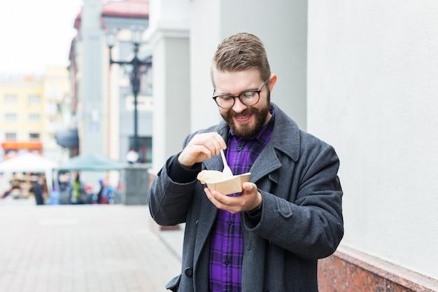 Крупный план человека держит сэндвич с фалафелем в бумажном пакете. концепция здоровой уличной еды, восточная кухня.
