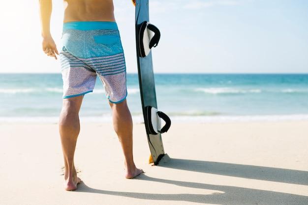 남자 다리 닫고 해변에서 보드.