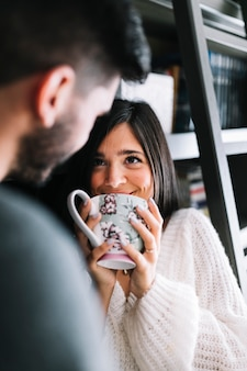 Close-up of man looking at smiling woman holding coffee mug