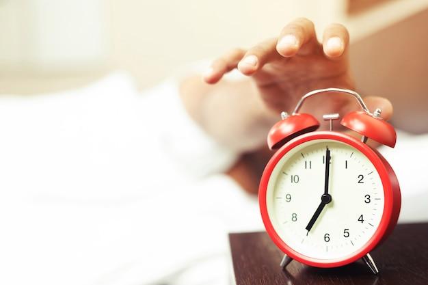 Закройте человека, лежащего в постели, выключая руку, тянущуюся к черному цвету будильника. просыпайтесь поздно утром в 7.20.