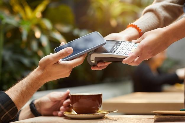 カフェで彼の注文のために携帯電話でオンラインで支払う男のクローズアップ
