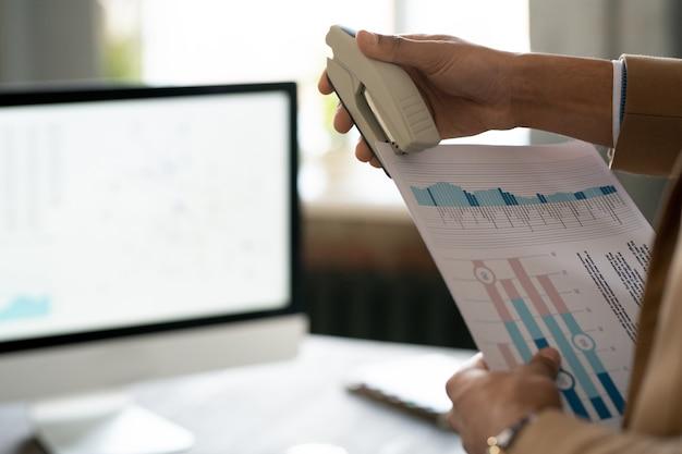 Крупный план человека, готовящего финансовый отчет и сшивающего документы степлером