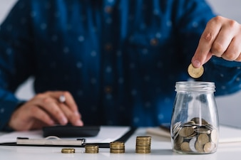 Close-up of man putting coins in jar using calculator at workplace