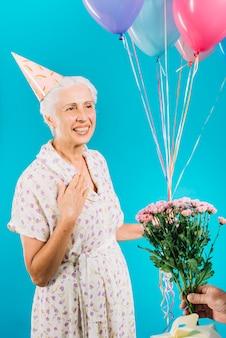 수석 여자에게 꽃과 생일 선물을주는 사람의 손의 근접