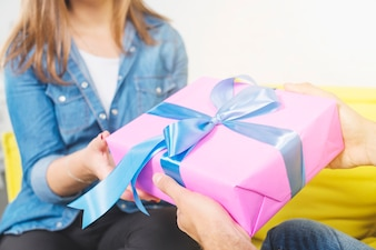 Close-up of man's hand giving gift to his girlfriend