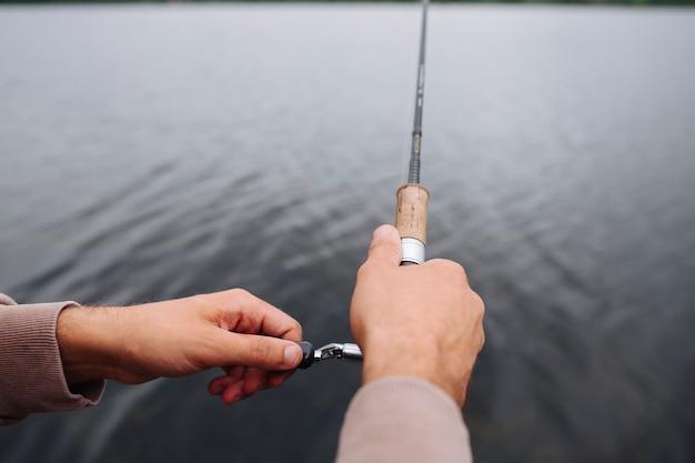 호수 위에 낚 싯 대를 잡고 남자의 손 클로즈업