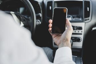 車の中の空のスクリーンで携帯電話を持っている男の手のクローズアップ