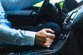 Close-up of man's hand shifting gear in car