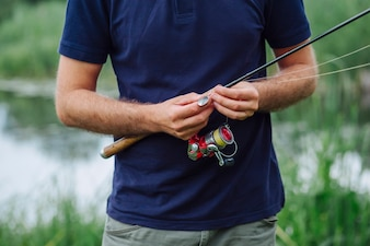 Close-up of man's hand tying fishing hook on fishing rod