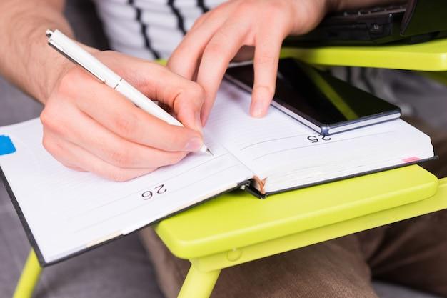 펜을 들고 소파에 앉아 집에서 그의 사업을 하는 노트북 테이블에 누워 일기에 약속을 하는 남자의 손 클로즈업