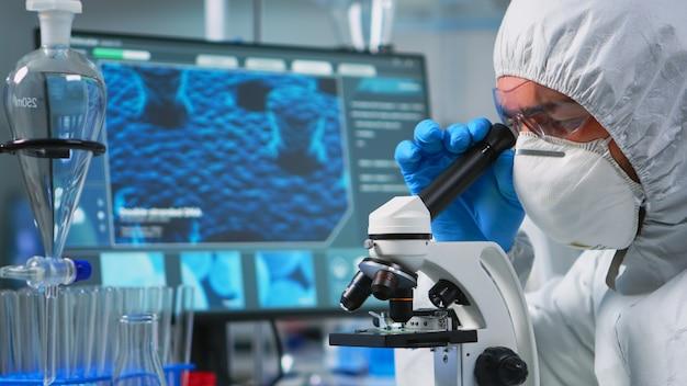 현대적인 장비를 갖춘 실험실에서 현미경을 들여다보는 남자 과학자의 클로즈업. covid19에 대한 치료 개발의 과학적 연구를 위해 첨단 기술을 사용하여 바이러스 진화를 조사하는 실험실 기술자