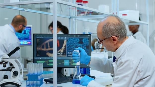 현대적인 장비를 갖춘 실험실에서 마이크로피펫을 사용하는 남자 과학자의 클로즈업. covid19 바이러스 개발 연구를 위한 첨단 화학 도구를 사용하여 백신 진화를 조사하는 다민족 팀