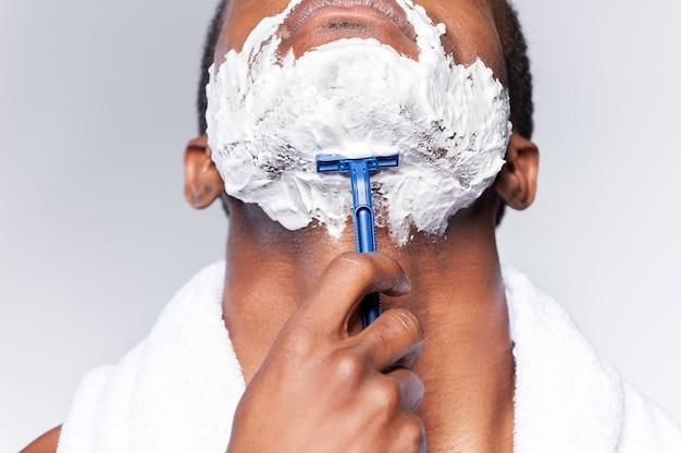 Крупным планом бритья человека. крупным планом молодого африканца, бреющего лицо, стоя на сером фоне