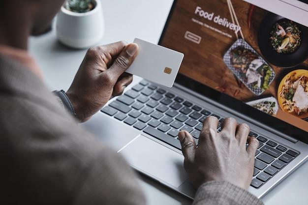 Крупный план человека, сидящего за столом перед ноутбуком с кредитной картой, заказывающего еду онлайн