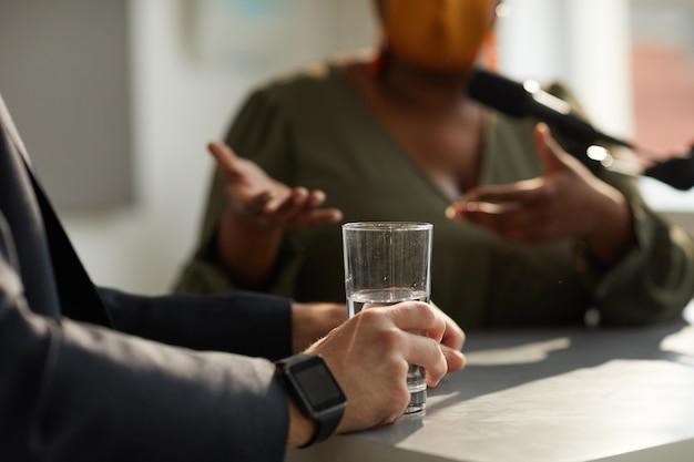 女性とのビジネス面接中に水のガラスとテーブルに座っている男性のクローズアップ