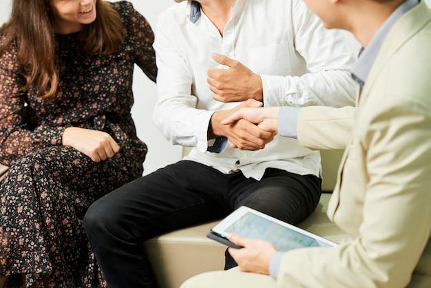 ソファで女性と一緒に座って、オフィスでの財務相談後のビジネスマンに握手する男性のクローズアップ
