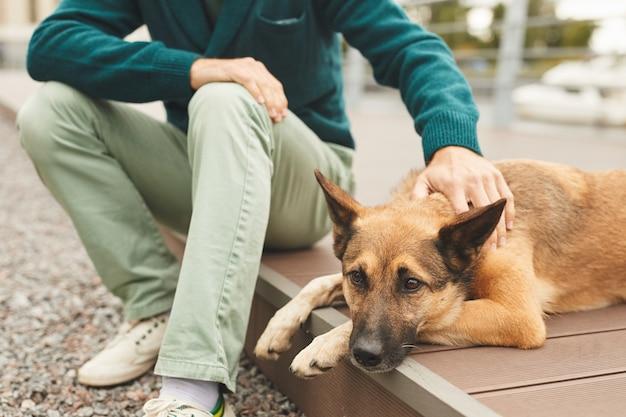 도시에서 걷고있는 땅에 누워있는 동안 개를 쓰다듬어주는 남자의 근접 촬영