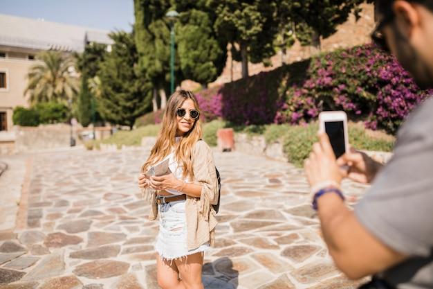 Крупным планом человек с фотографией стильной женщины, стоящей в парке