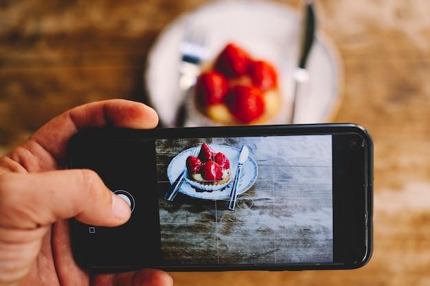ソーシャルメディアで共有し、いいねやフォロワーを受け取るために小さなストロベリーケーキの写真を撮っている男性のクローズアップ。人とインターネット技術。木製のテーブル