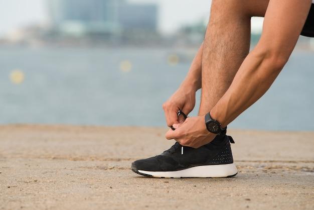 Крупный план человека, связывающего шнурки на открытом воздухе