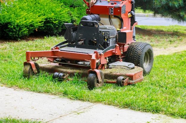 잔디 깎는 기계에 의해 잔디를 절단하는 정원사 잔디 깎는 기계를 사용하는 사람의 닫습니다