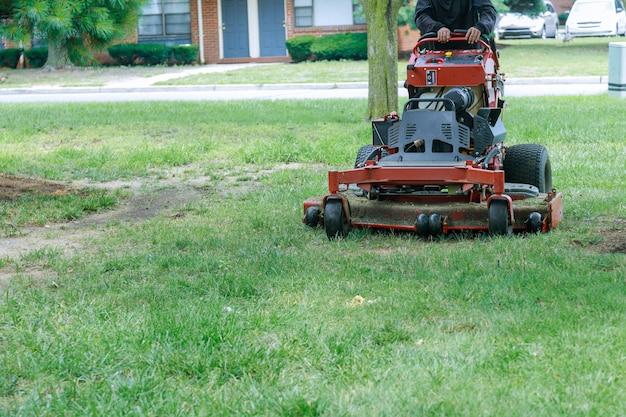 Крупным планом человека, использующего газонокосилку, садовник, режущий траву газонокосилкой