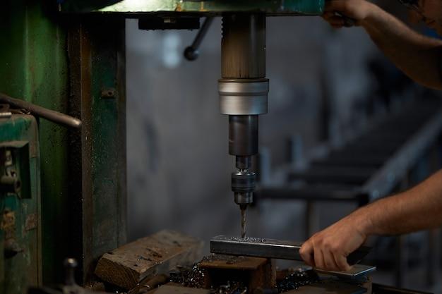 金属に穴を開けるためにドリルプレスを使用して男のクローズアップ