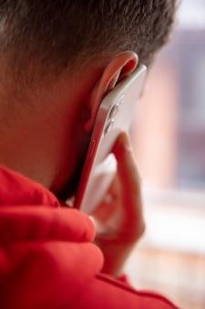 白い壁に隔離された携帯電話のスマートフォンを使用して男のクローズアップ。ライフスタイル、現代技術の概念。