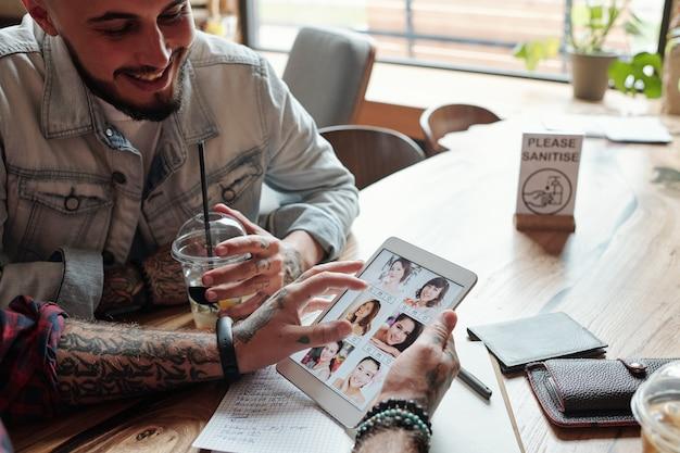 카페에서 친구에게 데이트 사이트에서 여자 프로필을 보여주는 동안 태블릿을 사용하는 남자의 근접