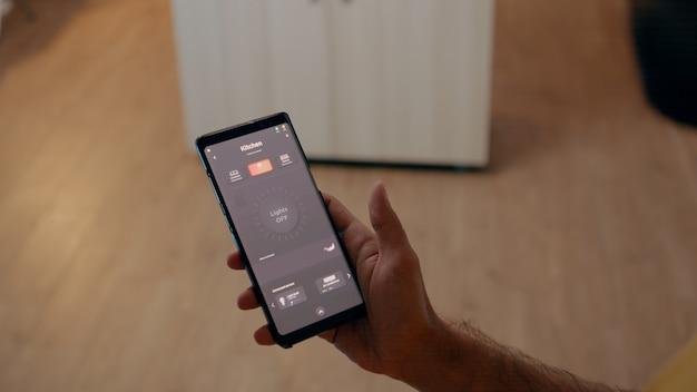 自動化システムを備えたスマートホームで電球をオンにするために音声起動アプリケーションを使用している男性のクローズアップ...