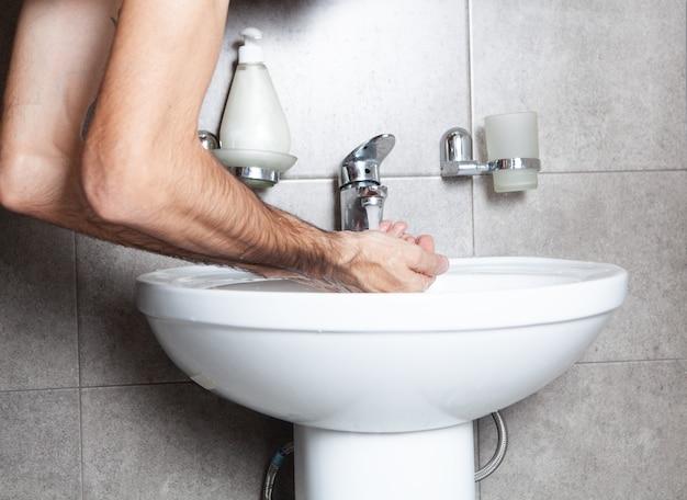 朝の流しで手を洗う男のクローズアップ
