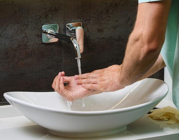 コロナウイルスコビッド19のパンデミックの保護のために石鹸で水の下で手を洗う人のクローズアップ