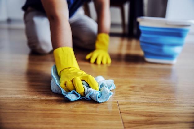 ワックスの寄木細工の床の男のクローズアップ。手にゴム手袋。ホームインテリア。