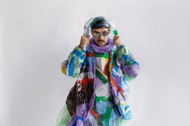 白い壁にプラスチックを身に着けている男のクローズアップ。ゴミで作られた服の男性モデル。ファッション、スタイル、リサイクル、エコ、環境のコンセプト。汚染が多すぎるので、私たちはそれを食べて飲んでいます。