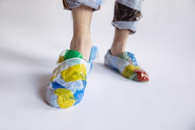 白い壁にプラスチックを身に着けている男のクローズアップ。ゴミで作られた靴の男性モデル。ファッション、スタイル、リサイクル、エコ、環境のコンセプト。汚染が多すぎるので、私たちはそれを食べて飲んでいます。