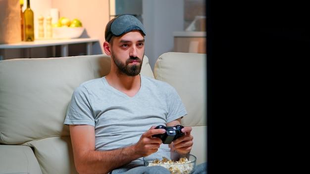 ジョイスティックでビデオゲームをプレイする目の睡眠マスクを持つ男のクローズアップ