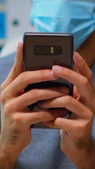 コロナウイルスの間に職場に座っているスマートフォンでテキストメッセージを入力するフェイスマスクを持つ男のクローズアップ。インターネット技術を使用して書くことを話している新しい通常のオフィスで働いているフリーランサー
