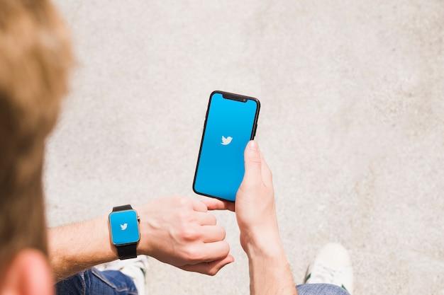 Крупный план человека с smartwatch и сотовый телефон, показывающий приложение twitter