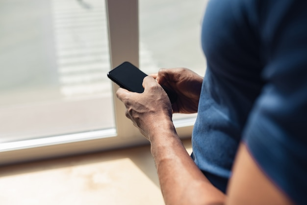 スマートフォンを使用して、オフィスで働く男性のクローズアップ