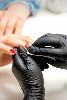매니큐어 마스터의 닫기 네일 살롱에서 보풀이없는 냅킨으로 여성 빨간 손톱 누수