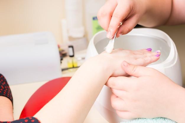 스파에서 고급 매니큐어를 하는 동안 왁스 워머 위에 작은 흰색 강모 브러시로 여성 고객의 손을 닦는 매니큐어사의 클로즈업