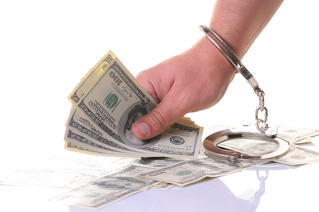 Крупным планом рука человека в закрытых металлических наручниках, держа стопку наличных денег в американских долларах, изолированных на белом фоне. незаконное получение денег, взятки, коррупция, преступления и наказания
