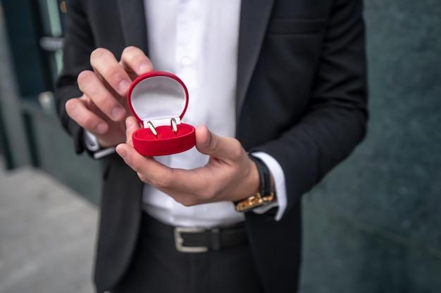 婚約指輪とボックスを保持している男の手のクローズアップ