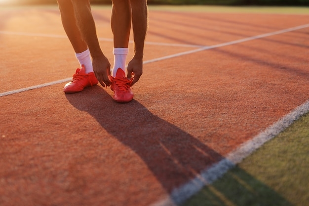 トレーニングの前に靴ひもを結ぶマンの手のクローズアップ。