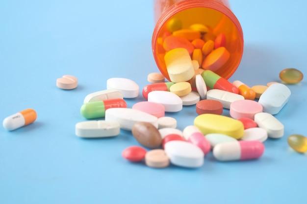 青い表面の多くのカラフルな錠剤やカプセルのクローズアップ